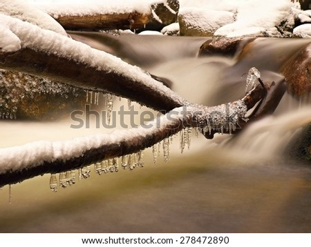Freeze winter view to icicles on twigs and icy boulders above rapid stream. Reflections of head lamp in icicles. - stock photo