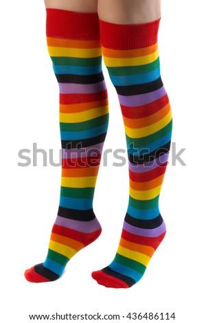 Freezing feet in colorful stockings isolated on white background. - stock photo