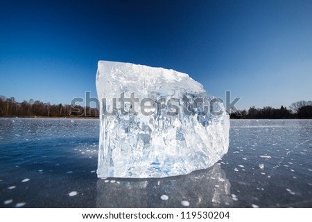 Freezing winter temperatures: block of ice lying on the surface of a frozen pond on a sunny winter day - stock photo