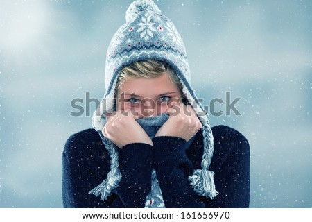 freezing young woman hiding behind her scarf in snowfall - stock photo
