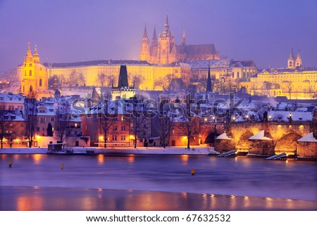 Freezy foggy night snowy Prague with gothic Castle and Charles Bridge and St. Nicholas' Cathedral - stock photo