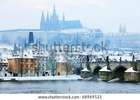 Freezy foggy snowy evening  Prague with gothic Castle and Charles Bridge