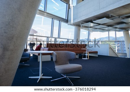 FREIBURG, GERMANY - OCTOBER: Images of the interior of the newly built University Library in Freiburg, Germany in 10/15. Images show modern concrete architecture and designer furniture with students. - stock photo