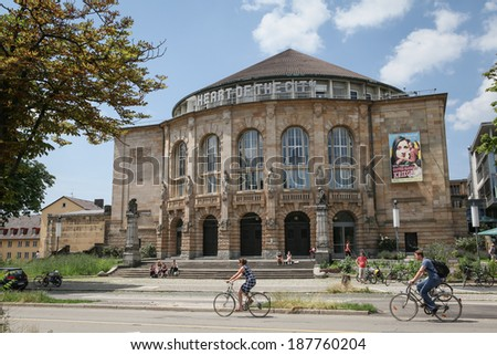 FREIBURG IM BREISGAU, GERMANY - JULY 6, 2013: Freiburg Theater in Freiburg im Breisgau with pedestrians passing by. The theater was built in 1823 and is the biggest and oldest theater in the city. - stock photo