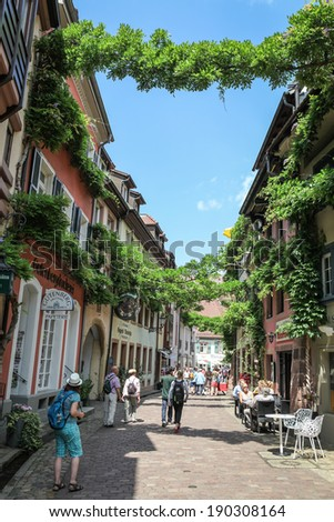 FREIBURG IM BREISGAU, GERMANY - JULY 6, 2013: Tourists on an old town street in Freiburg, a city in the south-western part of Germany in the Baden-Wurttemberg state. - stock photo