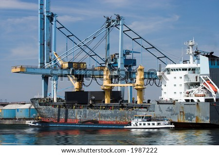 Freight being transferred from a large cargo ship to smaller vessels at Antwerp harbor (all brand names and logos have been removed) - stock photo