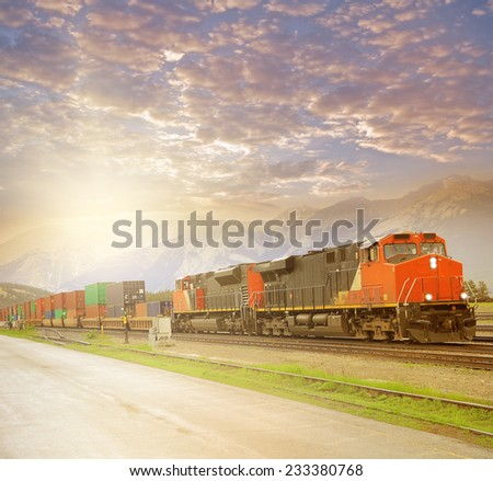 Freight train in Canadian rockies at sunset. - stock photo