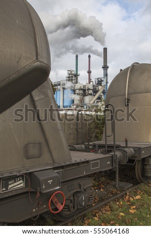 Freight train is standing still, factory with smoking chimney pipes in the background