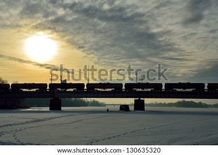 Freight train on the bridge during the sunrise - stock photo
