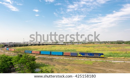 Freight train passing through green  field - stock photo