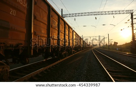 Freight train rides on the tracks at sunset