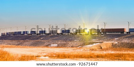 Freight train with cargo containers at sunset - stock photo