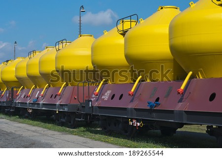 Freight Train with yellow tanks sitting on railroad tracks