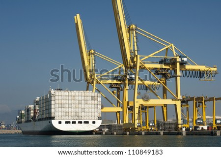 Freighter in port being loaded with containers.Cranes in port