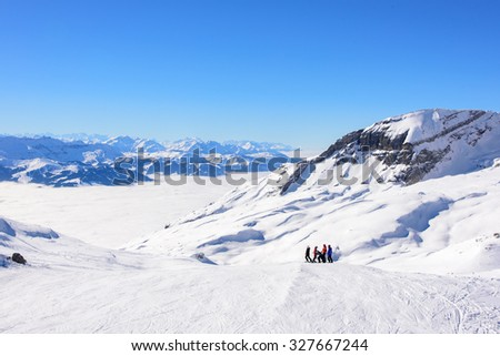 French and swiss alps above the clouds. A group of skiers have stopped to take in the view. Snowy alpine mountain ridge in the background.