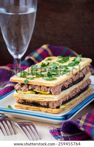 French appetizer millefeuille with eggplant, mousse, paste, cream of beans and meat - stock photo