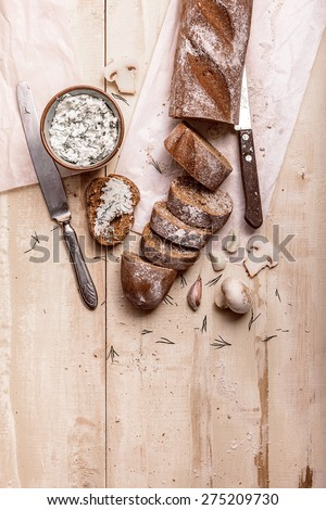 French baguette cut into pieces, garlic, ricotta cottage cheese and mushrooms on a rustic wooden board with knife over light old painted background. Top view - stock photo