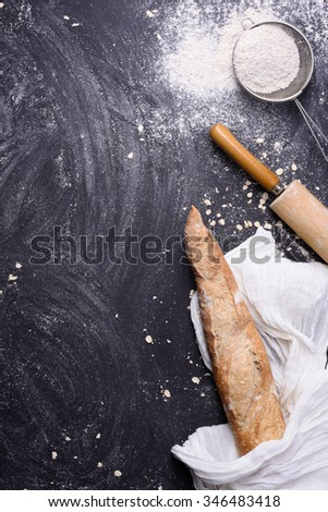 French baguette or rustic bread wrapped in white towel with rolling pin and flour over black background. Top view, copy space. - stock photo