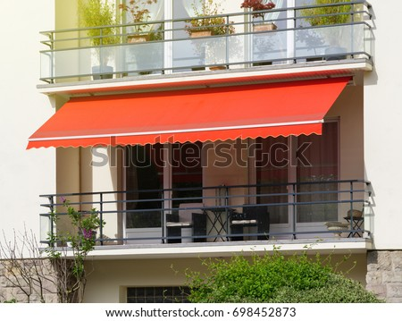 French Balcony With Awning Opened Covered By Sun Shield On A Warm Summer Day