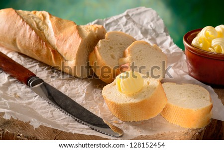French bread baguette (sliced) with knife and butter curls. - stock photo