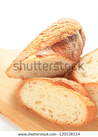 french bread,  sliced baguette on wooden chopping board - stock photo