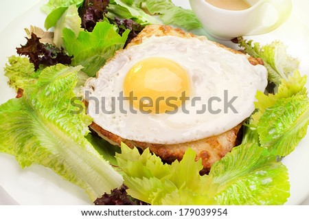 French breakfast Croque Monsieur, sauce and green salad with scrambled egg - stock photo