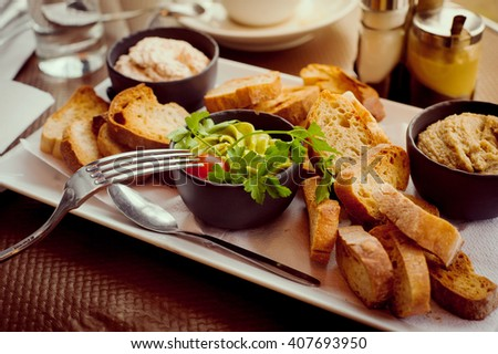 French breakfast for two in a Parisian street cafe - baguette, guacamole and salmon rillettes - stock photo