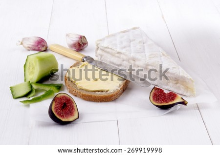 french camembert, slice bread with butter, fig, garlic, knife and peeled cucumber on white paper - stock photo