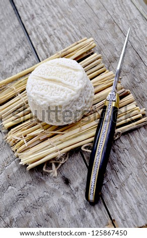 French cheese on a straw mat with decorative knife - stock photo