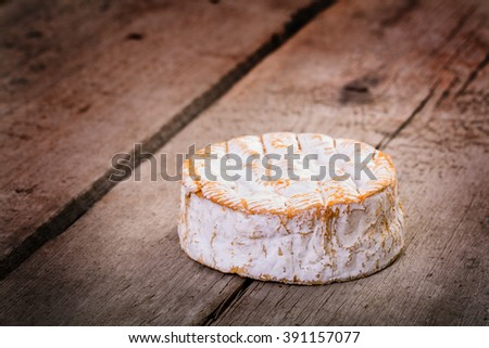 french cheese - round camembert, on old brown wood