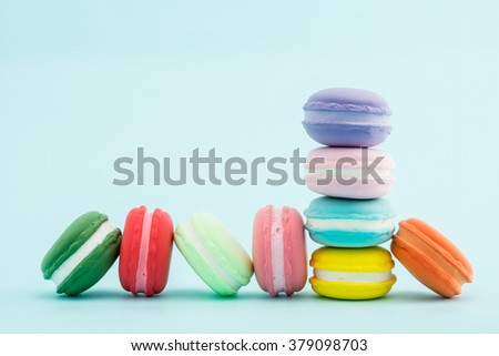 French colorful macarons stacks on pastel background, copy space