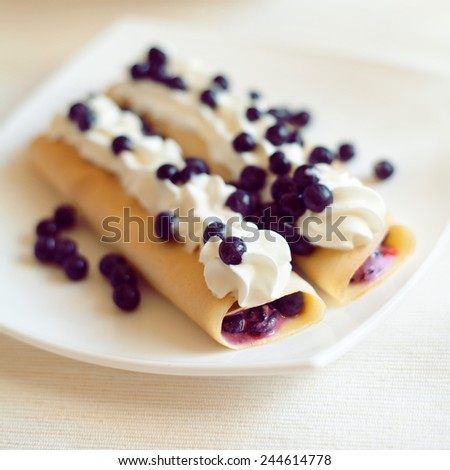 French crepes - thin pancakes with white cheese, blueberry fruits and whipped cream on white plate. - stock photo
