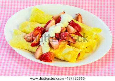 French Crepes with macerated strawberries and Greek Yogurt Sprinkled with powdered sugar.