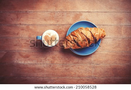 french croissant and cup of coffee on a wooden table - stock photo