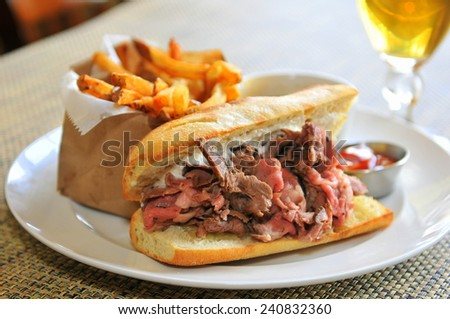 French Dip Sandwich - Juicy smoked prime rib sandwich on a crunchy French baguette smeared with horseradish sauce, and thinly sliced medium rare prime rib and Swiss cheese. - stock photo