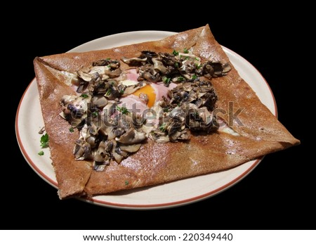 """french dish named """"Galette"""" on a plate in black back - stock photo"""