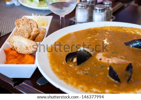 French fish soup Bouillabaisse served with pepper mayonnaise and toasted baguette. Selective focus. - stock photo