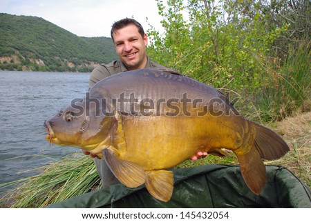 French fisherman holding a giant mirror carp. - stock photo