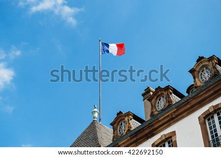 French flag above old City Hall in France - stock photo