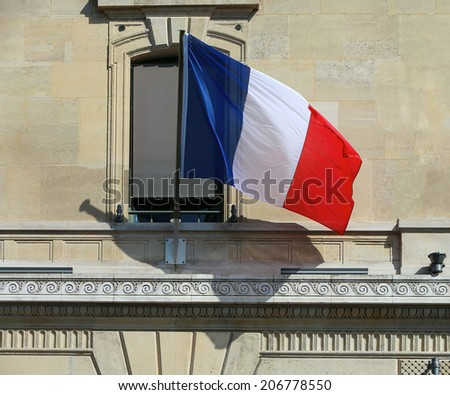 French Flag at Facade of Historic Building in Paris - stock photo