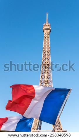 French flag in front of the Eiffel Tower in Paris France on a blue sky day. - stock photo