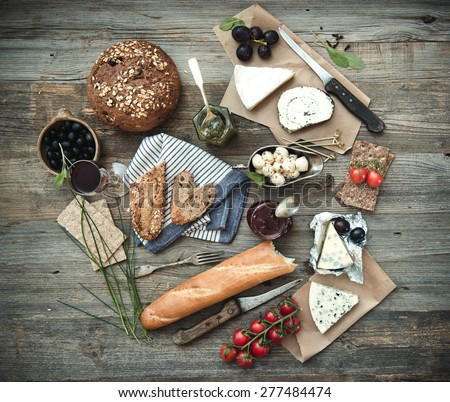 French food on a wooden background. Different types of cheese, wine and other ingredients on a wooden table - stock photo