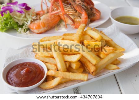 French fried on dish  with fried shrimp on background