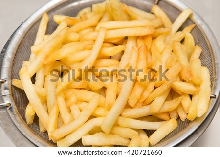 french fried on oil strainer - stock photo
