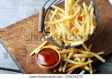 French fried potatoes in metal basket on wooden background - stock photo