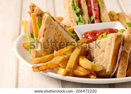French fries and club sandwiches in the plate on wooden background,selective focus - stock photo