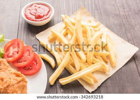 French fries and fried chicken on a wooden table. - stock photo