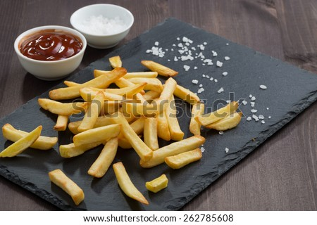 French fries and tomato sauce on a blackboard, horizontal - stock photo