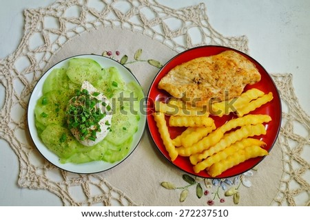 French fries, chicken breast and salad with cucumber