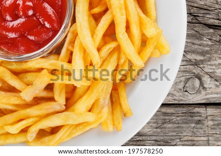 French fries closeup over wood - stock photo